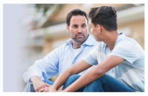 Man speaking to teenager
