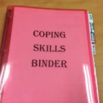 A binder with Coping Skills Binder written on it.
